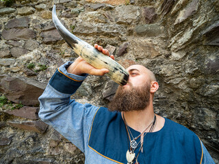 Portrait of a young warrior drinking from a Viking horn