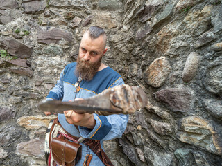 Portrait of a young Viking brandishing an ax in front of a stone wall