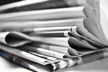 Stack of folded old newspapers, selective focus