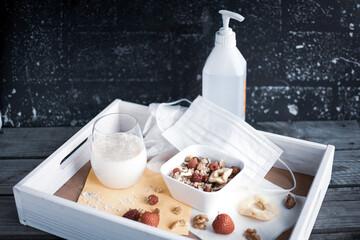 Holztablett mit gesundem Müsli, Hafermilch und Hygieneartikeln für Covid-19