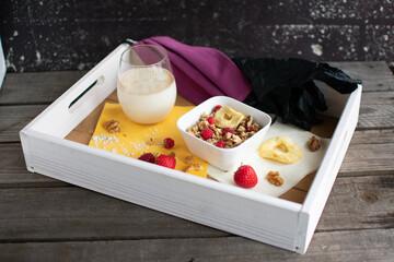 Frühstückstablett mit gesundem Müsli, Hafermilch, lila Mundschutz und Einweghandschuhen