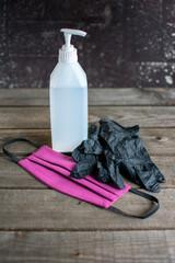 hygienekonzept: Zersträuber, lila Mundschutz und Einweghandschuhe auf Holz.