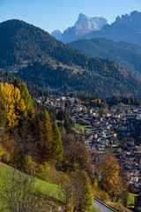 Autumn alpine Dolomites scene, Belluno, Sudtirol, Italy. Peaceful village  Falcade and rocky mountain tops view from road.