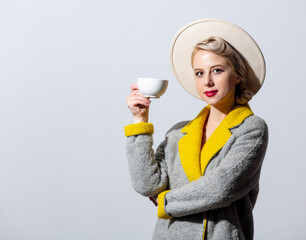 Blonde girl in grey coat and vintage hairdress with cup of coffee