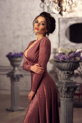 Young beautiful lady in evening dress posing in luxury interior and looking at you