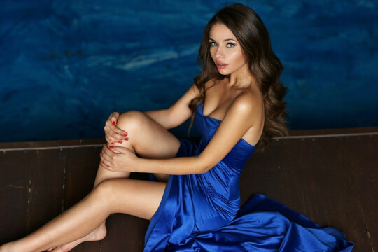 Fashion vogue style portrait of young beautiful stylish lady sitting on wooden floor. Sexy pretty woman in elegant evening blue dress