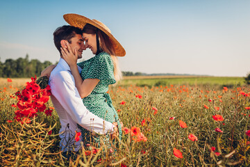 Loving couple walking in poppy field with bouquet of flowers. Happy man lifting woman having fun. Summer