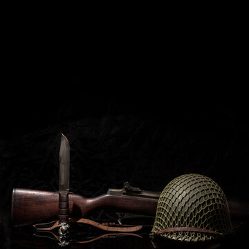 Still life symbolizing Memorial Day with a soldiier's helmet, a Garand M1 rifle, Marine Corps Ka-bar fighting knife and EGA.