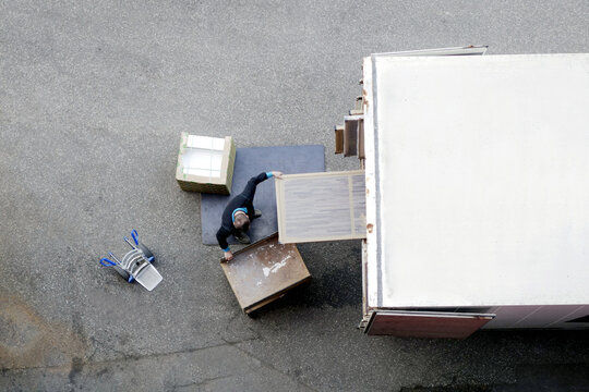 Mover unload furniture and boxes from moving truck. Situation with moving house worker, manually download the furniture from a back of a truck. View from above.