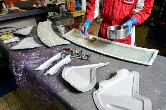 Installation of fiberglass: worker manually realizes a component in glass fiber for automotive use. Creating a spoiler for cars using a mold. View from above.