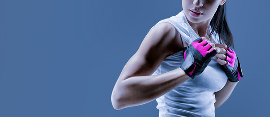 Conceptual close up portrait of fitness athletic young female model in sports clothing. Confident female bodybuilder with power hand in gloves over toned blue background