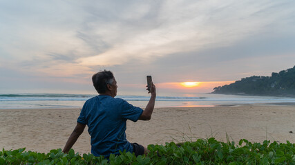 .A man sitting on the beach and selfie during sunset at Karon beach