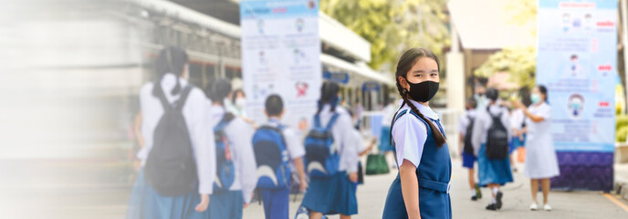 Asian child in school uniform wearing face mask with school bag and social distancing protect from coronavirus. Back to school for new normal lifestyle concept. panoramic banner with copy space