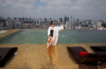 A woman poses for a photo at the gold plated infinity pool of the newly-inaugurated Dolce Hanoi Golden Lake luxury hotel, after the government eased a nationwide lockdown following the global outbreak of the coronavirus disease (COVID-19), in Hanoi