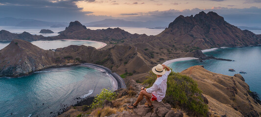 A traveller sitting on top of Padar island and talking picture of beautiful landscape at sunset, Flores island in Komodo national park, Indonesia in summer season. Panoramic banner portion