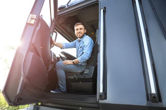 Male driver in cabin of big truck