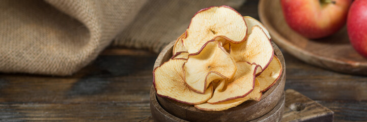Apple chips in a wooden bowl. Dried apples for a healthy diet. Apple chips close-up. Banner with space for text