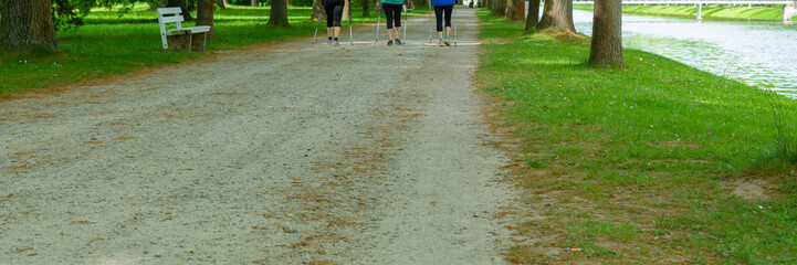 Three unrecognizable people walking in the park, panorama