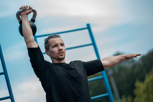 young athlete has workout and doing sport exercises with kettlebell outdoor