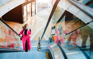 beautiful woman bright coat rides escalator shopping center black protective mask on her face against the virus polluted air.