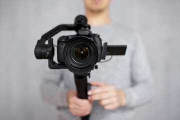 close up of modern dslr camera on 3-axis gimbal stabilizer in male videographer hands over grey