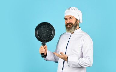 Professional kitchenware. Teflon might be toxic. Nonstick pan for frying. Enameled cooking vessels. Man hold pan. Frying meal. Healthy food. Bearded chef preparing breakfast. Frying without oil