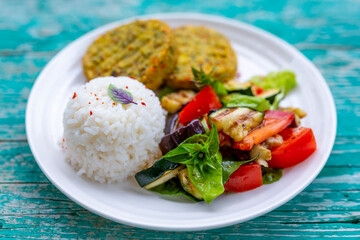 Vegetarian burgers with a healthy salad and rice.