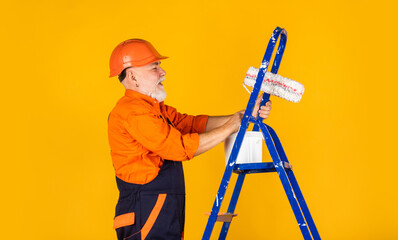 Builder engineer architect. man use roller on ladder. work in apartment. Craftsman With Paint Roller. House Painting and Renovation Business. making repair tool. Painter working at construction site