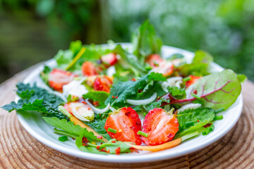 A healthy and delicious salad made from fresh strawberries and vegetable leaves. Vegetarian food.