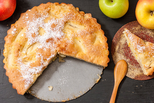 Tasty pie with apples on a wooden table. Homemade baking.