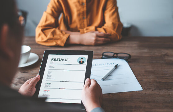 HR managers are interviewing job applicants who fill out their resume on the job application form in order to consider accepting a job as a company.