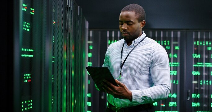 African American man, data base administrator in server room, tapping on tablet device and checking information on computer. Work with secret information. Big data storage. Digital defence concept.