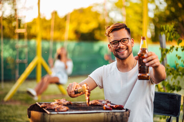 Outdoors portrait of a young man toasting with a bottle while preparing barbecue for friends.