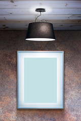 Photo frame mockup on rusty wall with ceiling lamp.