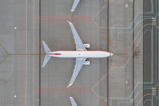Top down view on comercial airplane in the parking lot of the airport apron, waiting for services maintenance, refilling fuel services after airspace lock down