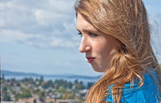 This is a portrait of a pretty Caucasian 17 year old teen girl.  She's outdoors and it's a head and shoulders image from the side view.  Beautiful blurred view in the background, model has a wholesome