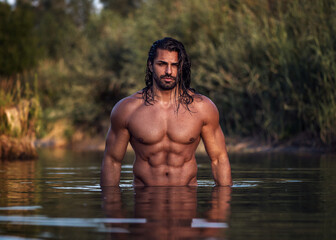 Long haired bearded muscular man shirtless stands waist deep in the water. Aquaman in the water. Tanned attractive guy with long dark wet hair