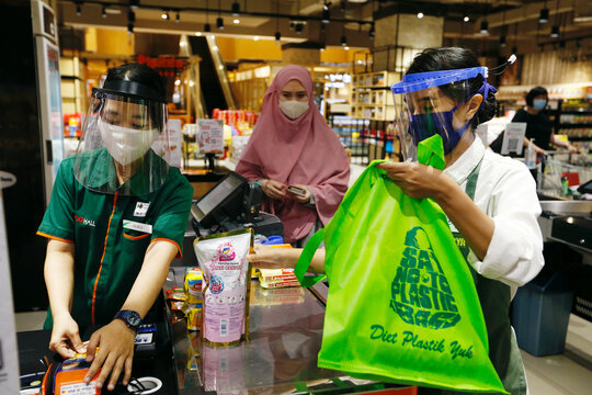 A worker wearing a face shield and protective mask use a tote bag to replace plastic at a supermarket in Jakarta