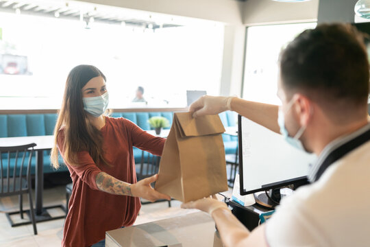 Woman Receiving Parcel From Takeout Counter