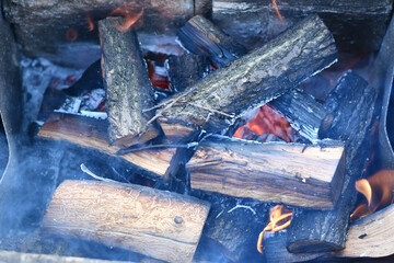 Poster Firewood texture burning firewood in a fireplace. Campfire from wooden logs in blue smoke with burning embers