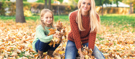 Happy young caucasian mother and little child playing with leaves in nature autumn park