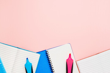 Back to school concept. Notepads and felt tip pens on pastel pink backdrop. Copy space, top view