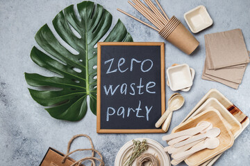 Zero waste party concept. Eco ffriendly tableware, craft bags and monstera leaves on gray...