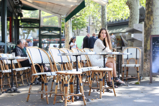 Nice young brunette woman in white dress sits alone in street cafe in Paris