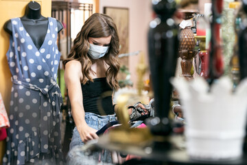 Teen Girl Wearing Face Mask Shopping For Clothing