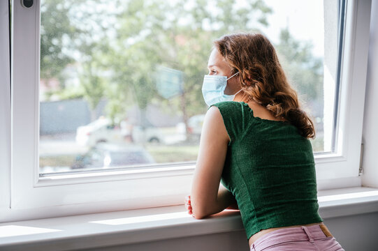 Young woman in quarantined face mask looking out the window