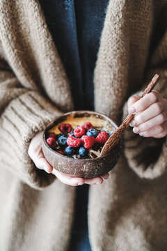 Healthy vegan breakfast bowl. Overnight oats, mango smoothie and fresh berries in coconut shell natural bowl and spoon in womans hands. Vegan, vegeratian, clean eating, dieting, weight loss concept