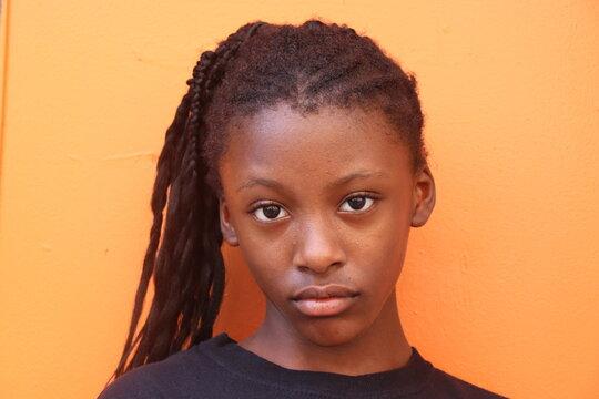 Black girl close up orange wall background