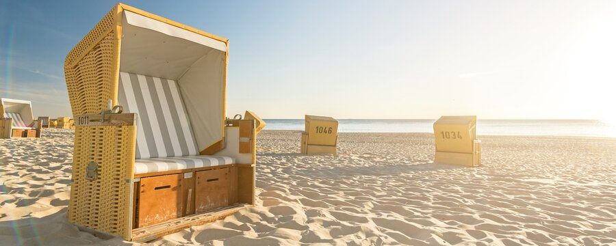 Beach chairs at the ocean with scenic lens flare during the sunset on the island of Sylt in Germany (banner format)