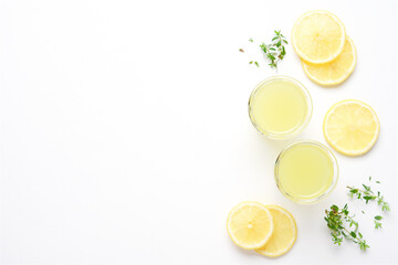 Lemon slices and glasses of limoncello on white background. Top View Bright Summer Alcohol Drink Concept